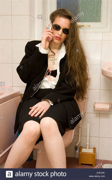 woman using mobile phone whilst sitting on toilet Stock